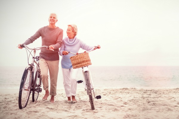 couple walking bikes on beach